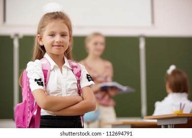 Little blonde girl studying at school class