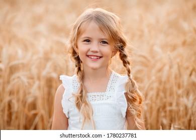 Little blonde girl walks in a summer wheat field
