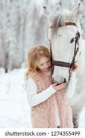 Little blonde girl with a white horse