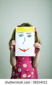 Little blonde girls holding happy face mask