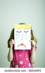 Little blonde girls holding sad face mask