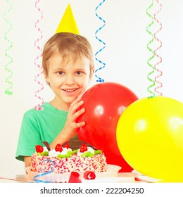 Little blonde kid in holiday cap with a birthday cake and balloons
