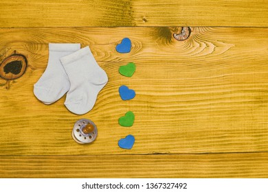 Little blue baby boy socks with pacifier and heart shapes on wooden table.Baby announcement concept.Toned photo.