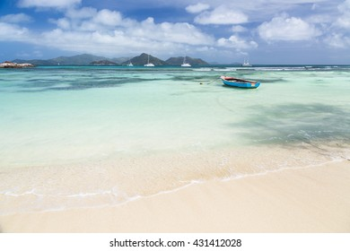 A little blue boat in a lagoon in La Digue, Seychelles with view to Praslin