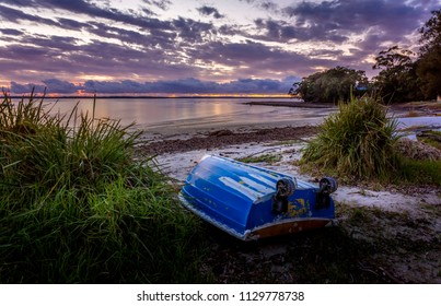 "Little blue rowboat, sometimes called ""tinnies"" in Australia sits upturned on a beach at dawn with the sky aglow with the first colours of morning"