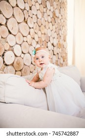 little blue-eyed girl blond in a white tulle dress with a decoration on her head playing and rejoicing on a beige sofa in a room with a decorative wooden wall in the form of hemp.