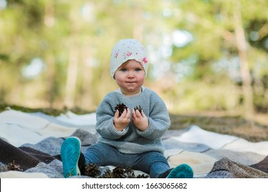 little blue-eyed girl in gray clothes sits in the forest and plays with pine cones