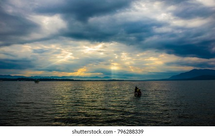 Little boat in the vast lake and the light thought from cloud in early morning