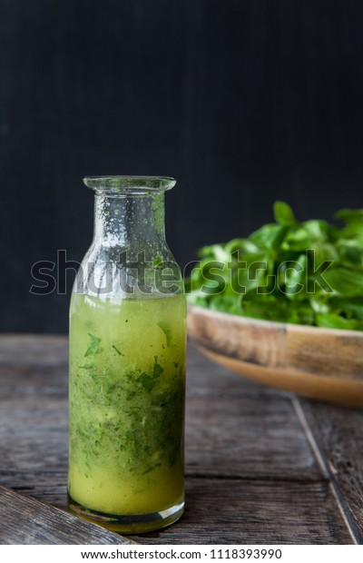Little bottle with homemade salad dressing with fresh parsley