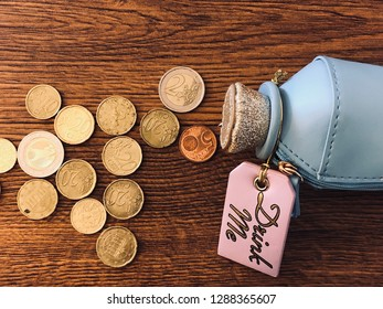 A little bottle on a wooden table with coins