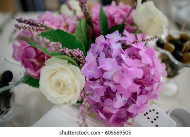 Little bouquet of pink hydrangeas and white roses stands on dinner table