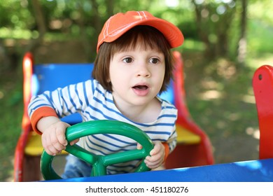 Little boy (2.11 years) drives car on playpit in summer