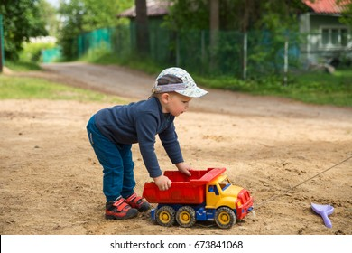 Little boy 2-3 years old, playing outdoors with a plastic truck