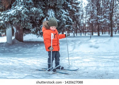 Little boy is 3-4 years old, winter on children's skis, first steps skis, active image of children. Background snow drifts trees. Free space. The idea of happy childhood in the fresh air in nature