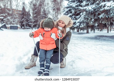 A little boy of 3-5 years old, gets up on skis for the first time, in the winter in a snowy forest. A young mother holds a child in the back. Active skiing, nature on a winter day. Happy smiles.