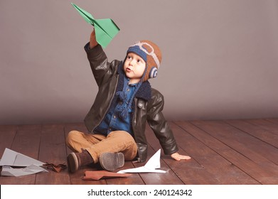 Little boy 4-5 year old playing with paper planes in room. Wearing stylish leather jacket and knitted pilot hat over gray.