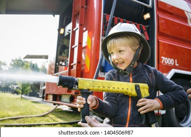 Little boy acting like a fireman holding firehose nozzle and splashing water.