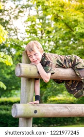 A little boy with ADHD, Aspergers Syndrome, Autism climbing in the park and having fun dressed as a little soldier