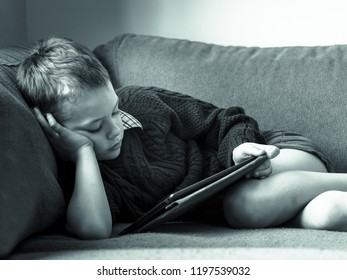 A little boy with ADHD, Autism, Asperger syndrome reading a book on the sofa after breaking his leg and having it put in a cast at the hospital