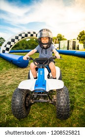 Little boy with ADHD, Autism, Aspergers Syndrome riding a quad bike and having fun, crash helmet and visor on