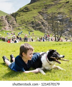 A little boy with ADHD, Autism, Aspergers Syndrome playing with his loyal pet dog in the Derbyshire Peak District and the famous Dovedale stepping stones