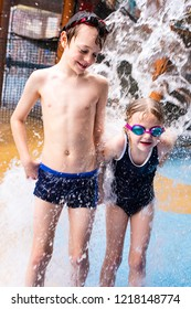 A little boy with ADHD, Autism, Aspergers Syndrome playing with his sister under a high water jet, laughing and being happy