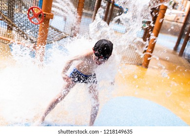 A little boy with ADHD, Autism, Aspergers Syndrome playing under a high water jet, laughing and being happy