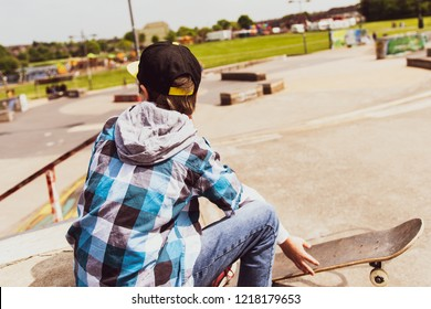 A little boy with ADHD, Autism, Aspergers Syndrome, enjoys a day at the skatepark, listening to music and skateboarding, wearing a baseball cap and shirt