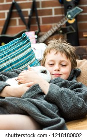 A little boy with ADHD, Autism, Aspergers Syndrome cuddles his pet rabbit, bonding, caring and kind