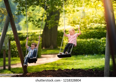 A little boy with ADHD, Autism, Aspergers Syndrome, playing on a swing with his little sister on a beautiful sunny day