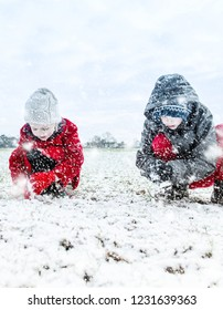 A little boy with ADHD, Autism, Aspergers Syndrome playing in the heavy snow fall with his sister making snow balls