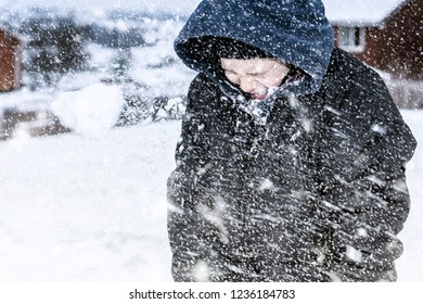 A little boy with ADHD, Autism, Aspergers Syndrome playing in the heavy snow fall, making snow balls, snowing at Christmas, Xmas, Christmas Eve