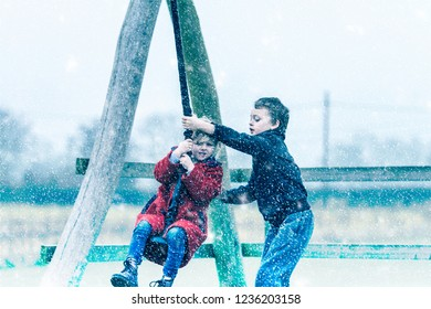 A little boy with ADHD, Autism, Aspergers Syndrome playing in the heavy snow fall with his sister at the park having fun