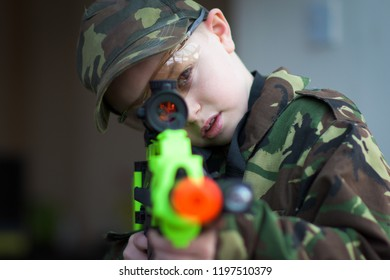 A little boy with ADHD, Autism poses in camouflage (DPMs) with his BB gun, rifle outdoors playing in the wild, Asperger syndrome