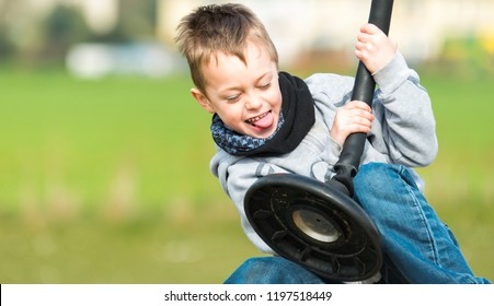 A little boy with ADHD, Autism poses playing on a swing full of happiness and joy, Asperger syndrome