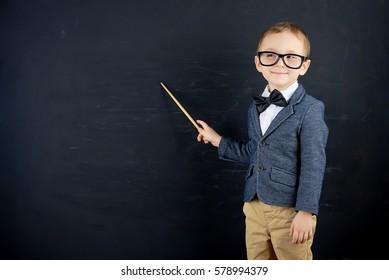Little boy against blackboard. School concept