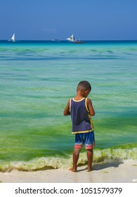 Little boy alone in shallow water of Boracay beach, Philippines, yachts and turquoise sea in background