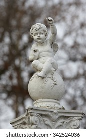 little boy angel sculpture sits on the ball and gesticulates