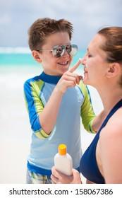 Little boy applying sun cream to her mother nose