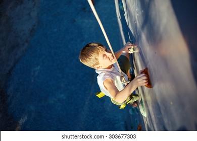 Little boy ascending in outdoor rock climbing gym