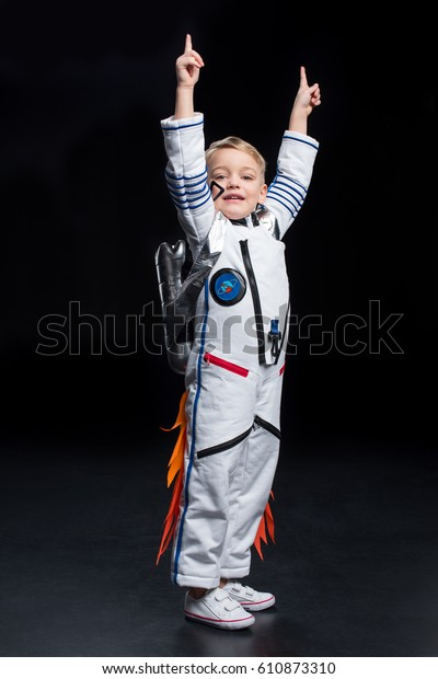 Little boy astronaut in space suit pointing up with fingers on black