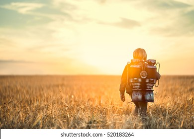 Little boy with a backpack at sunset