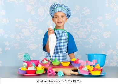 Little boy is baking colorful cupcakes with vintage wall paper in background
