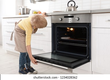 Little boy baking cookies in oven at home