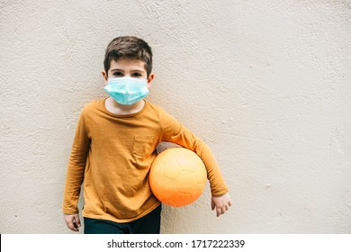 Little boy with a ball and protective mask. Coronavirus concept.