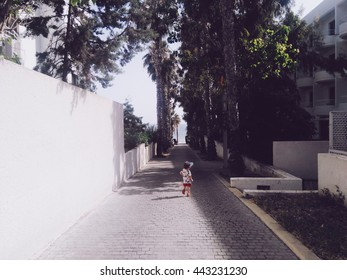 Little boy in baseball hat running on the street on Cyprus island Paphos town. Palms alley with sea at the background. Family travel with children. Mobile photo.