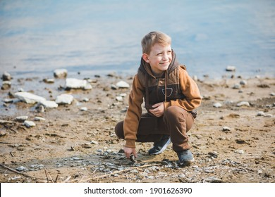 little boy at beach trowing rocks into water. outdoors activities