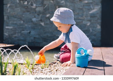 Little boy in beautiful zen garden with watering can near fountain. Child playing outdoors in spring or summer. Family on nature in Arboretum, Slovenia.