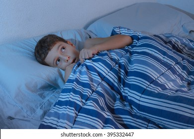 Little boy in the bed scared, hiding under the blanket at night