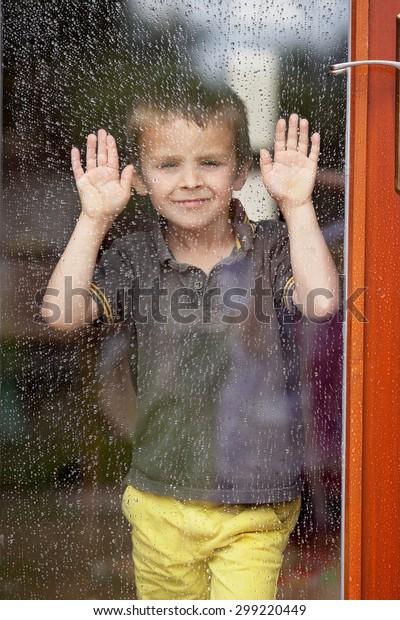 Little boy behind the window in the rain, looking sad